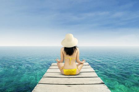 Meditation - Yoga woman meditating at serene beach photo