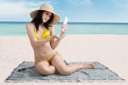 Sexy woman putting sunblock before sunbathing on beach photo