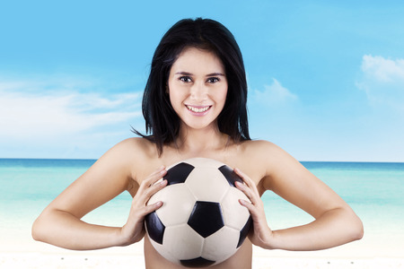 Portrait of sexy woman smiling while holding soccer ball at beach photo