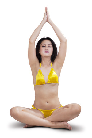 A healthy young woman sitting in a yoga position meditating photo