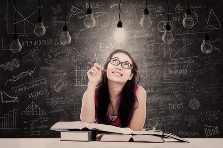 lit lamp: Beautiful young student is looking at bright lit lamp with written blackboard behind her