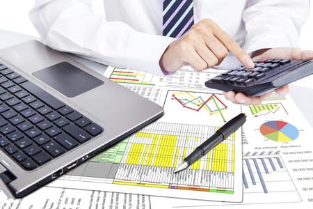 Close up of businessman working with calculator photo