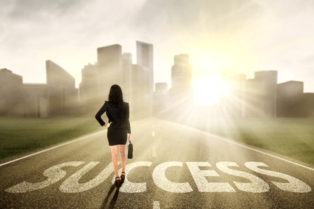 solutions freeway: Businesswoman looking for success and walking on the highway of a skyscraper with cityscape