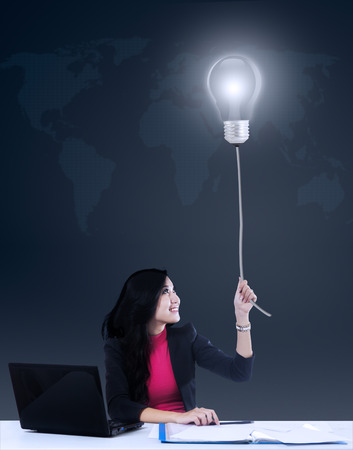 Young asian businesswoman grabbing a bright lamp photo
