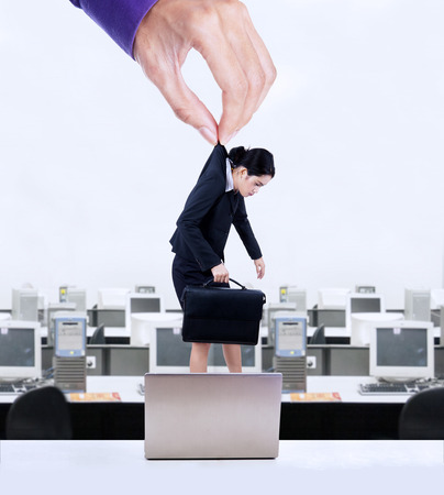 Businesswoman working like a robot controlled by hand at office
