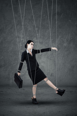 Businesswoman hanging on strings like marionette photo