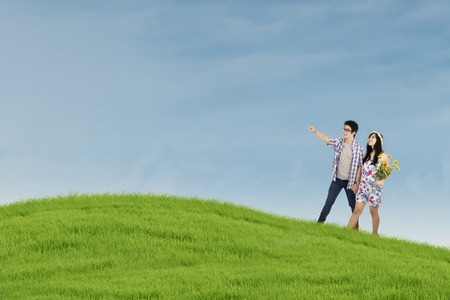 Romantic young couple walking on the green field photo