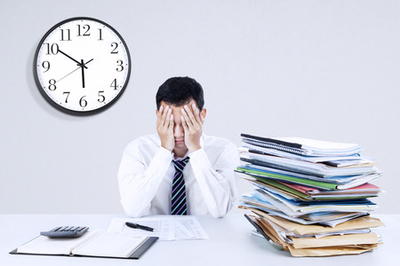 overwhelmed: Portrait of exhausted young businessman sitting at office desk