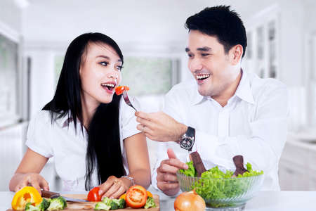 Happy couple making vegetables salad in the kitchen photo