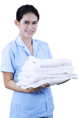 Smiling young cleaning lady holding towels isolated on white background