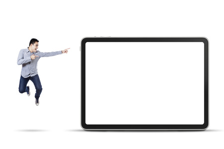 Happy asian man pointing at empty board, isolated on white background photo