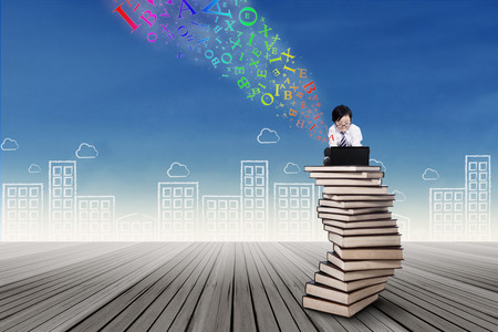 child sitting: Little child sitting on the top of book stack with laptop Stock Photo