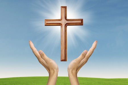 Male hands praying with a wooden cross on green field of grass - easter concept photo