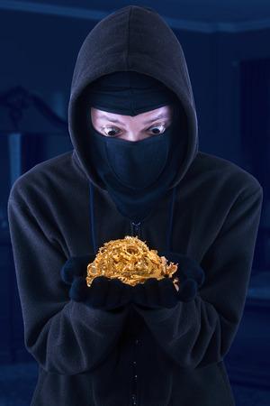 hijacker: Portrait of masked man is holding stolen gold