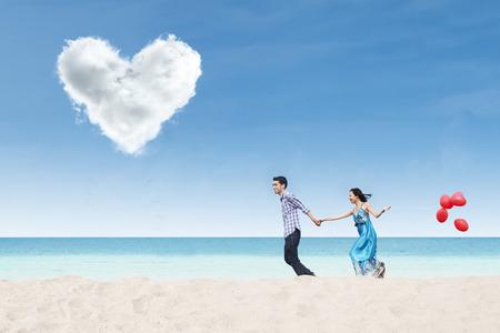under heart: Running couple on beach under heart cloud