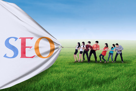 seo concept: Portrait of business team pulling together a banner of SEO