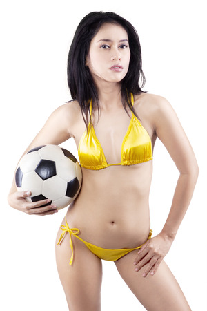Portrait of sexy woman wearing bikini holding a soccer ball. isolated on white photo