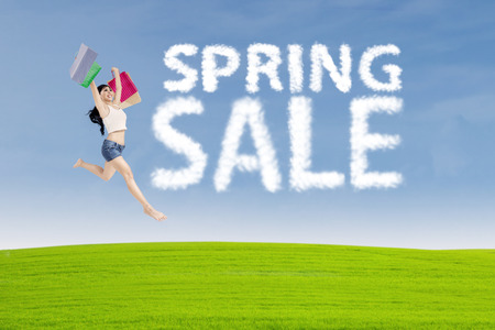 Happy woman jumping over green grass with cloud design of spring sale sign photo