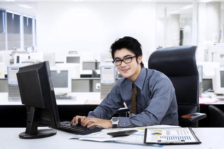 Retrato del encargado joven que trabaja en la oficina mientras se escribe en el teclado Foto de archivo - 27244893