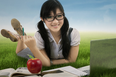 Female student studying with laptop and book at the park photo