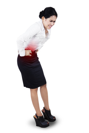 unease: Young businesswoman having stomach ache. isolated on white background Stock Photo