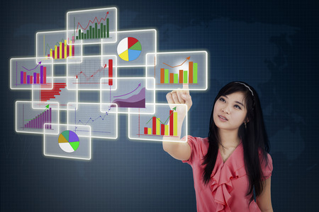 Businesswoman choosing one of business graph on futuristic touchscreen  photo