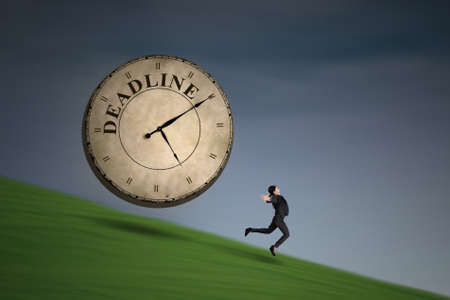 employe: Businesswoman is running with a deadline clock on green field  Stock Photo