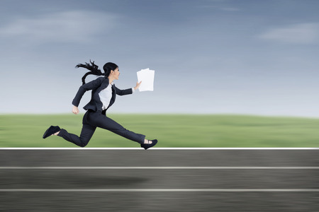 The young beautiful businesswoman runs by holding business paper photo