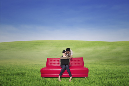 Romantic couple using laptop on red sofa outdoor photo