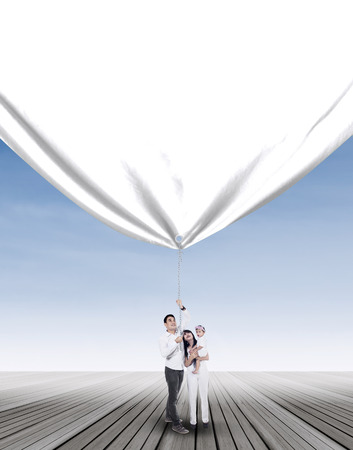 Young happy family is pulling blank banner outdoor photo