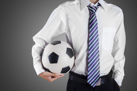 Elegant businessman holding a soccer ball, close up photo