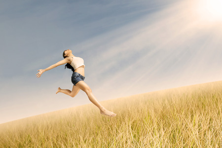 Happy young woman jumping on the air photo