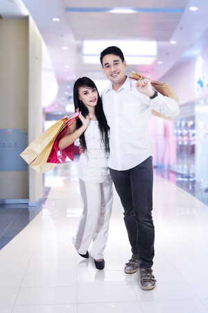 Happy couple with shopping bags in a shopping mall photo
