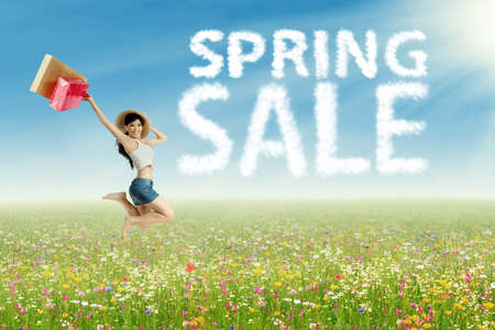 Portrait of shopaholic jumping on the meadow with spring sale clouds photo