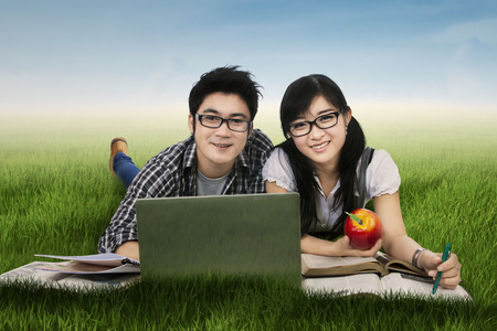 Young couple lying on grass while studying with laptop photo