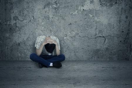 hombre solitario: Hombre joven desesperado sentado solo en el piso Foto de archivo