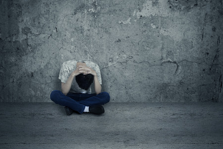 Young man hopeless sitting alone on the floor photo