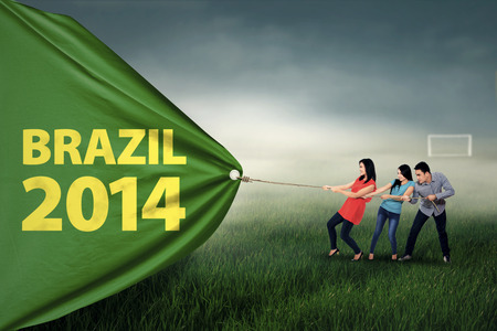 Group of people pull soccer a championship banner of the year 2014 at brazil
