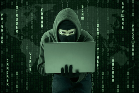 criminals: Hacker typing on a laptop with binary code background