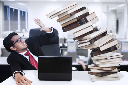 computer problem: Stress businessman and falling books at office with PC and laptop