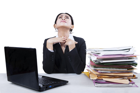 Businesswoman having sore throat while working at office photo
