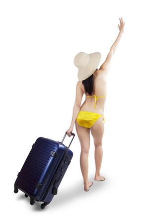 femme valise: Portrait en pied d'une belle jeune femme marchant avec une valise sur un fond blanc