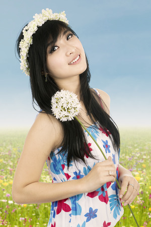 Beautiful woman with crown of flower holding flower photo