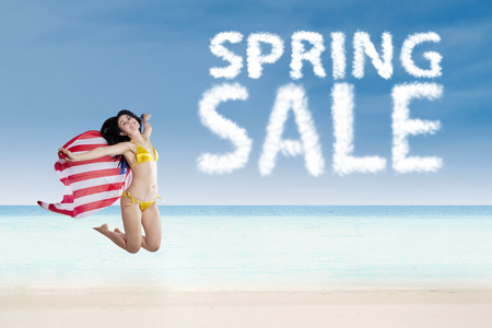 hawaii flag: Girl jumping beside spring sale cloud while holding American flag on the beach