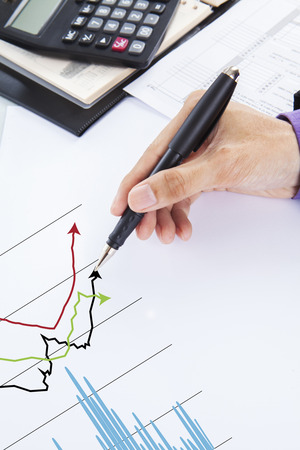 Businessman drawing financial charts for analyzing profit photo