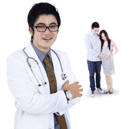 Young male doctor standing in front of a pregnant woman and her husband photo