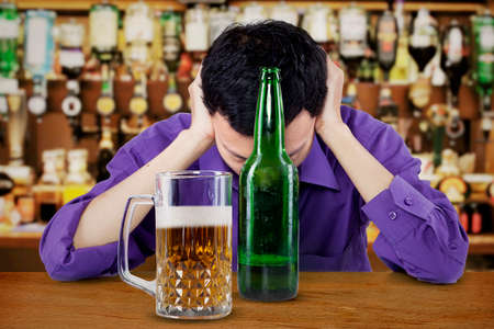 boozer: Drunk businessman with beer on the table in a bar