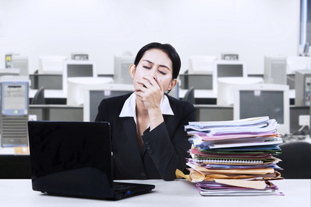 yawning: Exhausted attractive businesswoman working with her notebook sitting at her desk