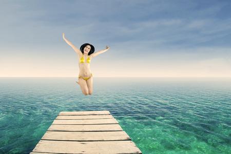 Happy woman wearing bikini jumping on the jetty at beach photo