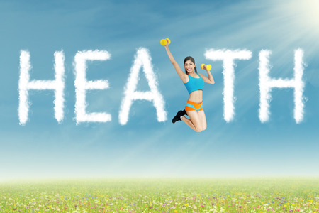 Sportswoman jumping with clouds shaped health photo